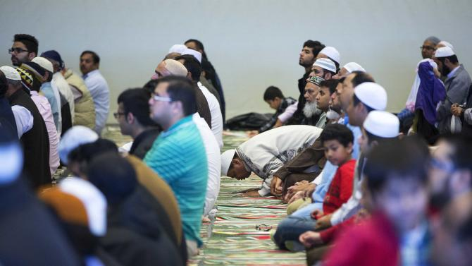 A Muslim prays during a memorial service for two Canadian soldiers killed in Eastern Canada this week, in Calgary