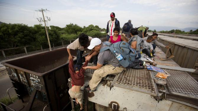 In this July 12, 2014, photo, a young boy is helped down from a freight car, as Central American migrants board a northbound freight train in Ixtepec, Mexico. Many smugglers take their charges from the southern Chiapas or Oaxaca states to Mexico City on La Bestia, the decrepit freight train, and from there, they choose one of three main routes: to Reynosa in Tamaulipas, Ciudad Juarez in Chihuahua, or cross the Sonoran desert to the outskirts of Mexicali. (AP Photo/Eduardo Verdugo)