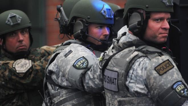 Metro SWAT members hang off the back of a truck as they prepare to search the School and Walnut Street neighborhood for one remaining suspect in Watertown, Mass.
