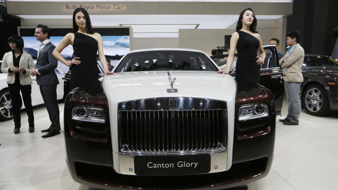 FILE - In this Nov. 21, 2013 file photo, models pose beside the Rolls-Royce Canton Glory at the company's booth during Guangzhou 2013 Auto Show in China's southern city of Guangzhou. Britain-based Rolls-Royce on Tuesday, July 8, 2014 said that global sales in the first half of the year were up 33 percent compared with the same period in 2013. (AP Photo/Kin Cheung, File)