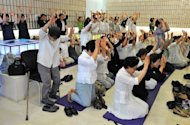 "Unification Church followers gesture as they recite the words ""True father, long live for billions of years!"" during a memorial service mourning the death of their leader Sun Myung Moon, in the church's Seoul headquarters, on September 5. Moon died of complications from pneumonia on September 3, aged 92"