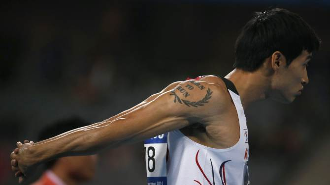 "South Korea's Cho Kyu-won, sporting a tattoo that says ""born to run"", stretches before the start of the men's 200m round one, heat four at the Incheon Asiad Main Stadium during the 17th Asian Games"