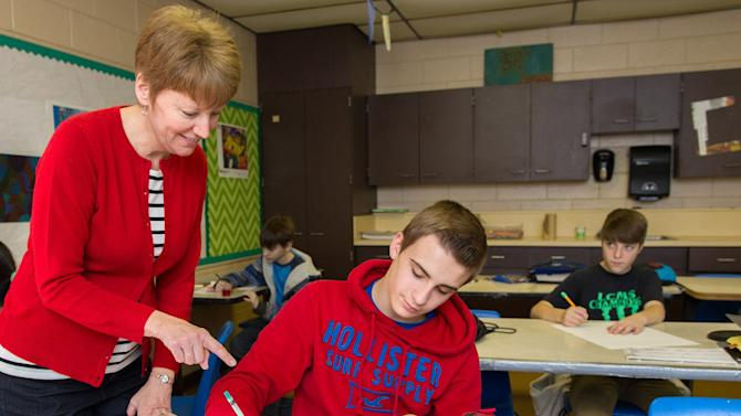 "In this undated photo, Nancy Smith, an art teacher at Livingston County Middle School, helps 8th grader Bryce Stein, with a drawing in Burna, Ky. Smith, who teaches art at the middle school and at Livingston County High School, said she's had her middle school students depict their own pieces titled ""The Street Where I Live"" based on the style of San Francisco artist John Kraft's ""Lombard Street"" for about five years. (AP Photo/The Paducah Sun, Ellen O'Nan)"