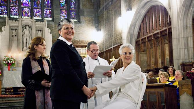 In this photo provided by Outserve-SLDN, Brenda Sue Fulton, center left, and Penelope Gnesin, hold hands while exchanging wedding vows at the U.S. Military Academy at West Point, N.Y., Saturday, Dec. 1, 2012. Their ceremony marks the first time a same sex couple had their wedding in the Cadet Chapel, the landmark gothic church that is a center for spiritual life at the Academy. The chaplain and woman at left are unidentified. (AP Photo/Outserve-SLDN, Jeff Sheng)