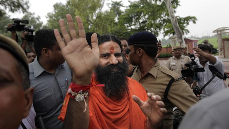 Indian yoga guru Baba Ramdev waves to the media as he leaves after paying homage at Rajghat, the memorial to late Mahatma Gandhi, before relaunching his anti-corruption protest in New Delhi, India, Thursday, Aug. 9, 2012. Ramdev on Thursday relaunched his indefinite agitation to press the government to act against widespread graft and bring back hundreds of billions of dollars stashed overseas. (AP Photo/Altaf Qadri)