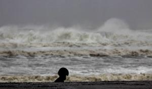 A man in a helmet walks past high waves of the Bay …