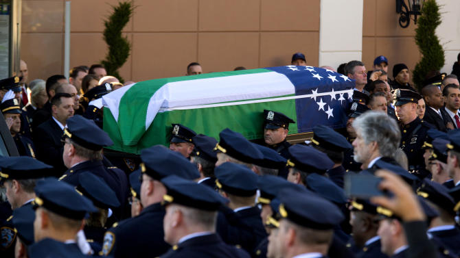 ADDS FLAG IS THAT OF THE NYPD - The body of New York City police officer Rafael Ramos is brought from Christ Tabernacle Church draped in an NYPD flag after his funeral in the Glendale section of Queens, where he was a church member, Saturday, Dec. 27, 2014, in New York. Ramos and his partner, officer Wenjian Liu, were killed Dec. 20 as they sat in their patrol car on a Brooklyn street. The shooter, Ismaaiyl Brinsley, later killed himself.  (AP Photo/Craig Ruttle)