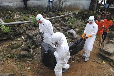 Health workers remove the body of Prince Nyentee, a man whom local residents said died of Ebola virus in Monrovia