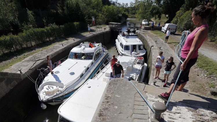 Tourists on river boats make their way along the Canal du Midi, in Paraza, southwestern France