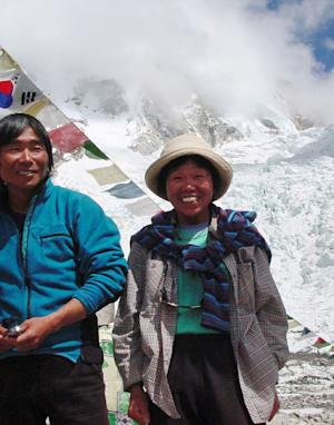 FILE - In this Thursday, May 9, 2002 file photo, Tamae Watanabe, right, of Japan poses with a photograher Noriyuki Muraguchi at a base camp on the foot of Mt. Everest in Nepal. A 73-year-old Watanabe has climbed Mount Everest, smashing her own record to again become the oldest woman to scale the world's highest mountain. (AP Photo/Office Seven Summits, File)