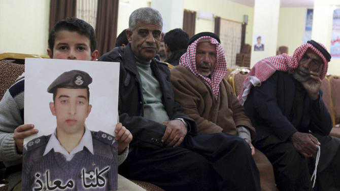 Relatives of Jordanian pilot Kasaesbeh, who was captured by Islamic State after his plane crashed during a bombing mission against them, hold pictures of him at the family's headquarters in Karak