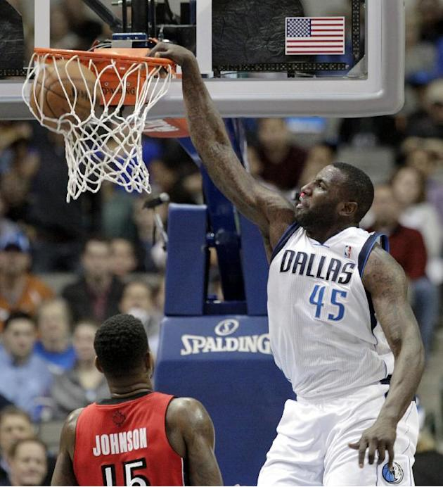 Dallas Mavericks' DeJuan Blair (45) dunks over Toronto Raptors' Amir Johnson in the first half of an NBA basketball game, Friday, Dec. 20, 2013, in Dallas