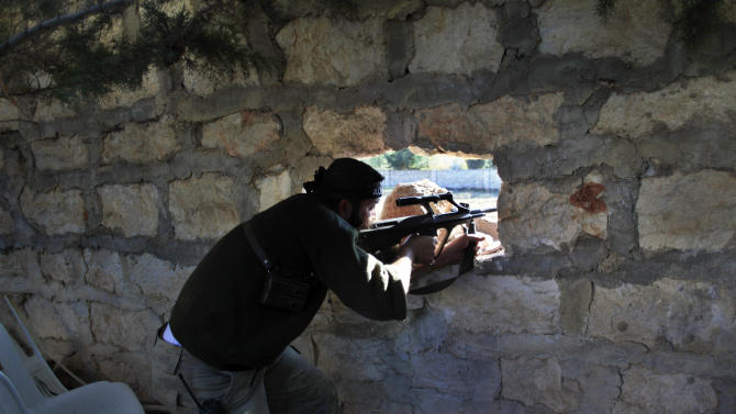 A Syrian rebel sniper aims at Syrian army positions on the outskirts of Aleppo, Syria, Wednesday, Nov. 14, 2012. Heavy clashes between rebel units and Bashar Assad's troops were ongoing in the northern city of Aleppo, the Syrian Observatory for Human Rights said Wednesday. (AP Photo/ Khalil Hamra)