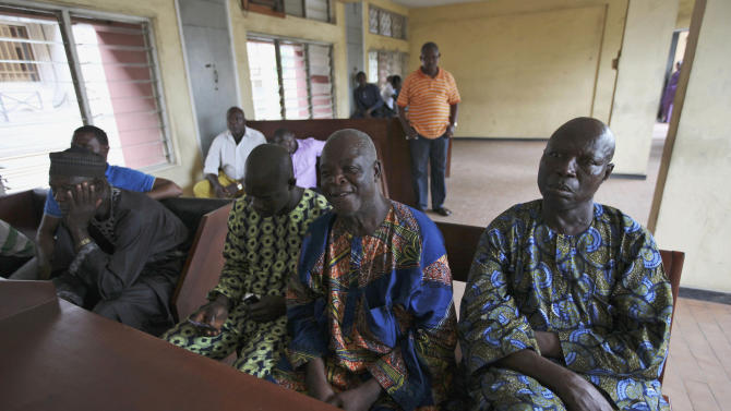 Men who claim that the were victims of crash attend a ruling at the Magistrate court in Lagos, Nigeria,  Wednesday, April 25, 2012. The failures of Africa's most populous nation seemed to explode into a fiery multiple car and truck crash in Nigeria that killed at least 18 people in 2010, according to a coroner's ruling issued Wednesday. Police set up an illegal checkpoint August 2010 along a major expressway in Lagos, using tires to funnel traffic down to one lane as officers demanded bribes from motorists, witnesses said. The driver of a speeding truck carrying sugar for the nation's largest industrial company tried to stop, but the vehicle's bad brakes failed and the truck slammed into waiting traffic, witnesses and officials said. Those details, long denied by authorities, came out Wednesday when a coroner investigating the deaths ruled against Nigeria's federal police and the Dangote Group, owned by billionaire Aliko Dangote.  (AP Photos/Sunday Alamba)