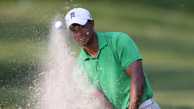Tiger Woods hits out of a bunker onto the 14th green during the third round of the AT&T National golf tournament at Congressional Country Club in Bethesda, Md., Saturday, June 30, 2012. (AP Photo/Patrick Semansky)