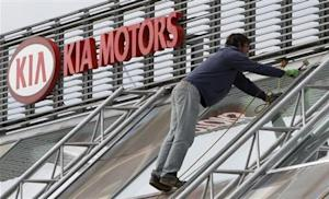 A worker repairs a roof next to a Kia Motors logo in Prague
