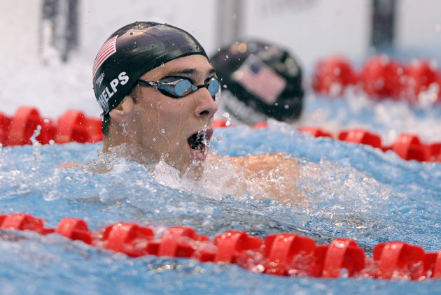 FILE - The Aug. 16, 2012 file photo shows United States' Michael Phelps reacting after winning the gold medal in the men's 100-meter butterfly final during the swimming competitions in the National Aquatics Center at the Beijing 2008 Olympics in Beijing. Whether it's Chinese-made uniforms for American athletes, a tattoo inked on a runner's body or a miniature American flag that can't go on Phelps' swim cap, Olympians should have figured out one thing by now: What they can or cannot wear at the London Games has very little to do with their fashion, marketing sense or patriotism, and a whole lot to do with rules, regulations and, of course, money.(AP Photo/Mark J. Terrill, File)