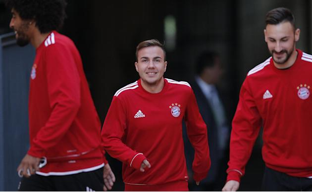 Bayern's Mario Goetze, center, arrives for a last training session between team mates Dante of Brazil, left, and Diego Contento at the Club World Cup soccer tournament in Marrakech, Morocco, Frida