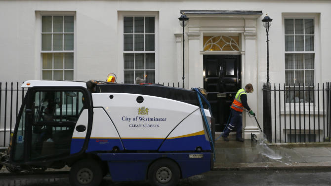 A cleaner washes the pavement in front of 11 Downing Street in London, Wednesday, March 20, 2013. Britain's Chancellor George Osborne will announce the Budget later Wednesday. (AP Photo/Kirsty Wigglesworth)