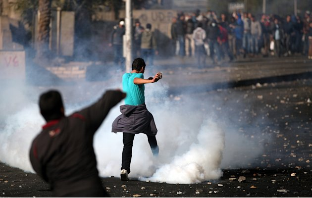 Pro and anti- government protesters clash near Tahrir Square, Cairo, Egypt,Tuesday, Jan. 29, 2013. Intense fighting for days around central Tahrir Square engulfed two landmark hotels and forced the U.
