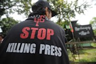 A Myanmar journalist wears a T-shirt reading &#39;Stop killing press&#39; as he waits outside a court for a ruling on a defamation case against &#39;The Voice Weekly&#39; in Yangon on August 23, 2012. The mining ministry filed a criminal defamation suit against The Voice Weekly, which reported that the auditor-general&#39;s office had discovered misappropriations of funds and fraud at the government division