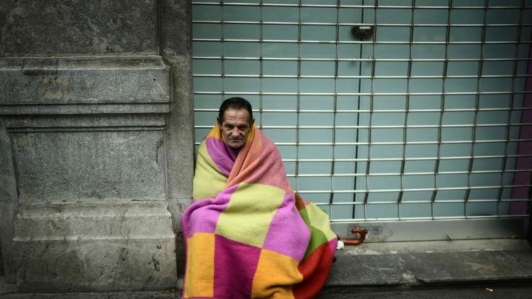 Lorenzo Fernandez Gonzalez, 64, sits wrapped in a blanket on the Gran Via of Bilbao
