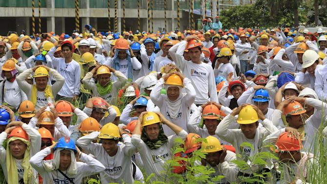 Construction workers take cover as they participate in the simultaneous earthquake drill in Manila