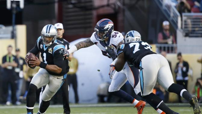 Carolina Panthers' quarterback Newton runs away from pressure from Denver Broncos' Ray as Panthers' Oher blocks during the second quarter of the NFL's Super Bowl 50 football game in Santa Clara