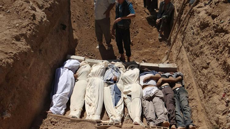 FILE - This image provided by by Shaam News Network on Thursday, Aug. 22, 2013, which has been authenticated based on its contents and other AP reporting, purports to show several bodies being buried in a suburb of Damascus, Syria during a funeral on Wednesday, Aug. 21, 2013. The early-morning barrage against rebel-held areas around the the Syrian capital Damascus immediately seemed different: The rockets made a strange, whistling noise. Seconds after one hit near his home, Qusai Zakarya says he couldn't breathe, and he desperately punched himself in the chest to get air. Hundreds of suffocating, twitching victims flooded into hospitals. Others were later found dead in their homes, towels still on their faces from their last moments trying to protect themselves from gas. Doctors and survivors recount scenes of horror from the alleged chemical attack a week ago. (AP Photo/Shaam News Network, File)