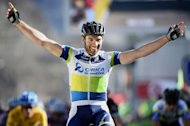 Team Orica Greenedge Swiss cyclist Michael Albasini celebrates while crossing the finish line of the fourth stage of the 71st Paris-Nice cycling race between Brioude and Saint-Vallier, on March 7, 2013