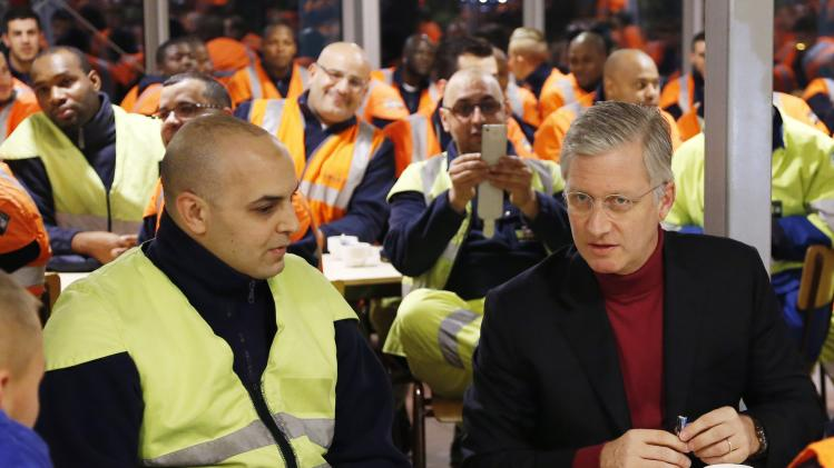 Belgium's King Philippe talks to garbage collectors during a visit to a depot of Brussels' garbage collection and recycling service