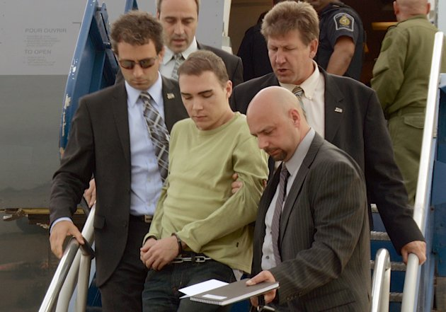 In this photo provided by Montreal Police, Luka Rocco Magnotta is taken by police from a Canadian military plane to a waiting van on Monday, June 18, 2012, in Mirabel, Quebec. Magnotta, the suspect in