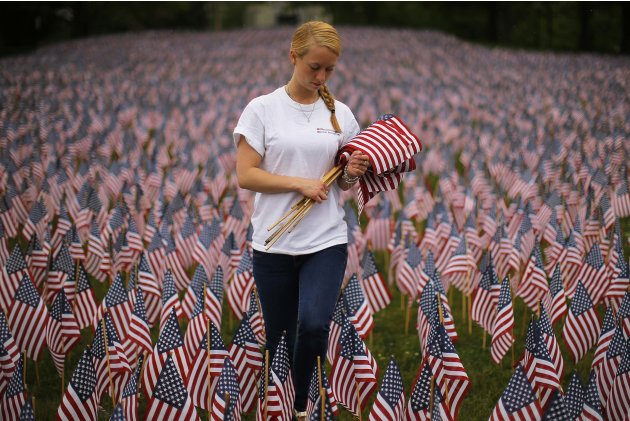 Day, volunteer with Massachusetts Military Heroes Fund, replaces broken flags at Memorial Day display of United States flags in Boston
