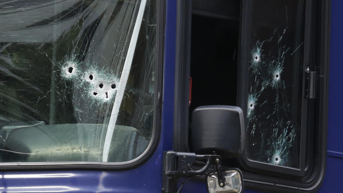 A King Co. Metro bus with multiple bullet holes in its windshield and side window, is seen in downtown Seattle after a bus driver was shot Monday, Aug. 12, 2013, in downtown Seattle. A man who had shot the driver of another bus was shot by officers after he boarded the bus shown here. (AP Photo/Ted S. Warren)