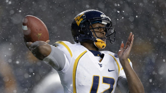 West Virginia quarterback Geno Smith passes in the snow against Syracuse during the second quarter of the Pinstripe Bowl NCAA college football game at Yankee Stadium in New York, Saturday, Dec. 29, 2012. (AP Photo/Kathy Willens)
