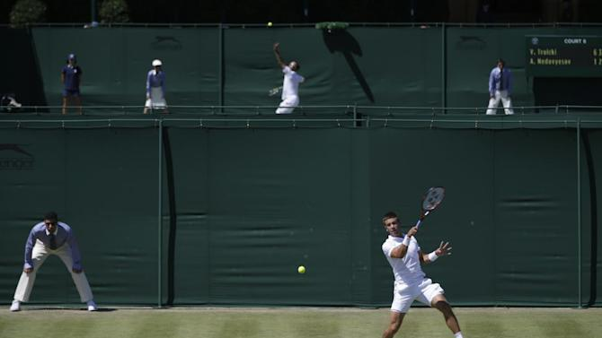 Borna Coric of Croatia returns a ball to Sergiy Stakhovsky of Ukraine during the singles first round match at the All England Lawn Tennis Championships in Wimbledon, London, Tuesday June 30, 2015. (AP Photo/Pavel Golovkin)