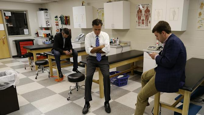 Republican presidential candidate and former Massachusetts Gov. Mitt Romney, center, sits in a training room with senior adviser Kevin Madden, left, and aide Garrett Jackson as they meet before the start of a campaign rally at Koehler Athletic Complex, University of Findlay, Sunday, Oct. 28, 2012, in Findlay, Ohio. (AP Photo/Charles Dharapak)
