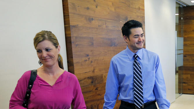 Thomas Beatie, and his girlfriend Amber Nicholas, leave their attorney's office, Tuesday, April 2, 2013, in Phoenix. Maricopa County Family Court Judge Douglas Gerlach ruled, March 29, 2013,  that Arizona's ban on same-sex marriages prevents Thomas Beatie's 9-year union from being recognized as valid.  Beatie was born a woman and later underwent a double-mastectomy, and began testosterone hormone therapy and psychological treatment to become a man, but he retained female reproductive organs and gave birth to three children. Gerlach said he had no jurisdiction to approve a divorce because there's insufficient evidence that Beatie was a man when he married Nancy Beatie in Hawaii. (AP Photo/Matt York)