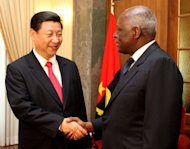 Chinese Vice-President Xi Jinping (L) shakes hands with Angolan President Jose Eduardo dos Santos (R) in 2010. Three dozen Chinese suspected of criminal acts against compatriots in Angola arrived in Beijing on Saturday under police guard as China targets crimes by its nationals overseas, state media reported