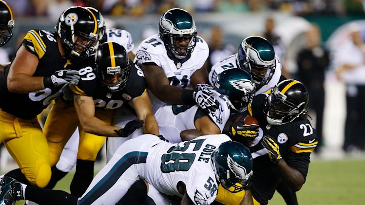 Pittsburgh Steelers' LeGarrette Blount (27) is tackled by Philadelphia Eagles' Trent Cole (58) and others during the first half of an NFL preseason football game, Thursday, Aug. 21, 2014, in Philadelphia. (AP Photo/Michael Perez)