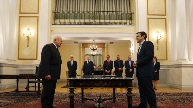 Head of radical leftist Syriza party and winner of the Greek parliamentary elections Tsipras stands in front of Greek President Papoulias in the Presidential Palace in Athens