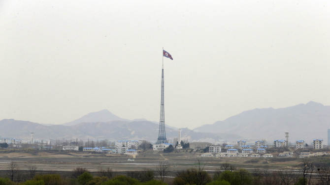 A giant North Korean flag atop a 160-meter (533-foot) tower flutters in the wind in North Korea near the border village of Panmunjom, which has separated the two Koreas since the Korean War, in Paju, north of Seoul, South Korea, Tuesday, April 23, 2013. (AP Photo/Lee Jin-man)