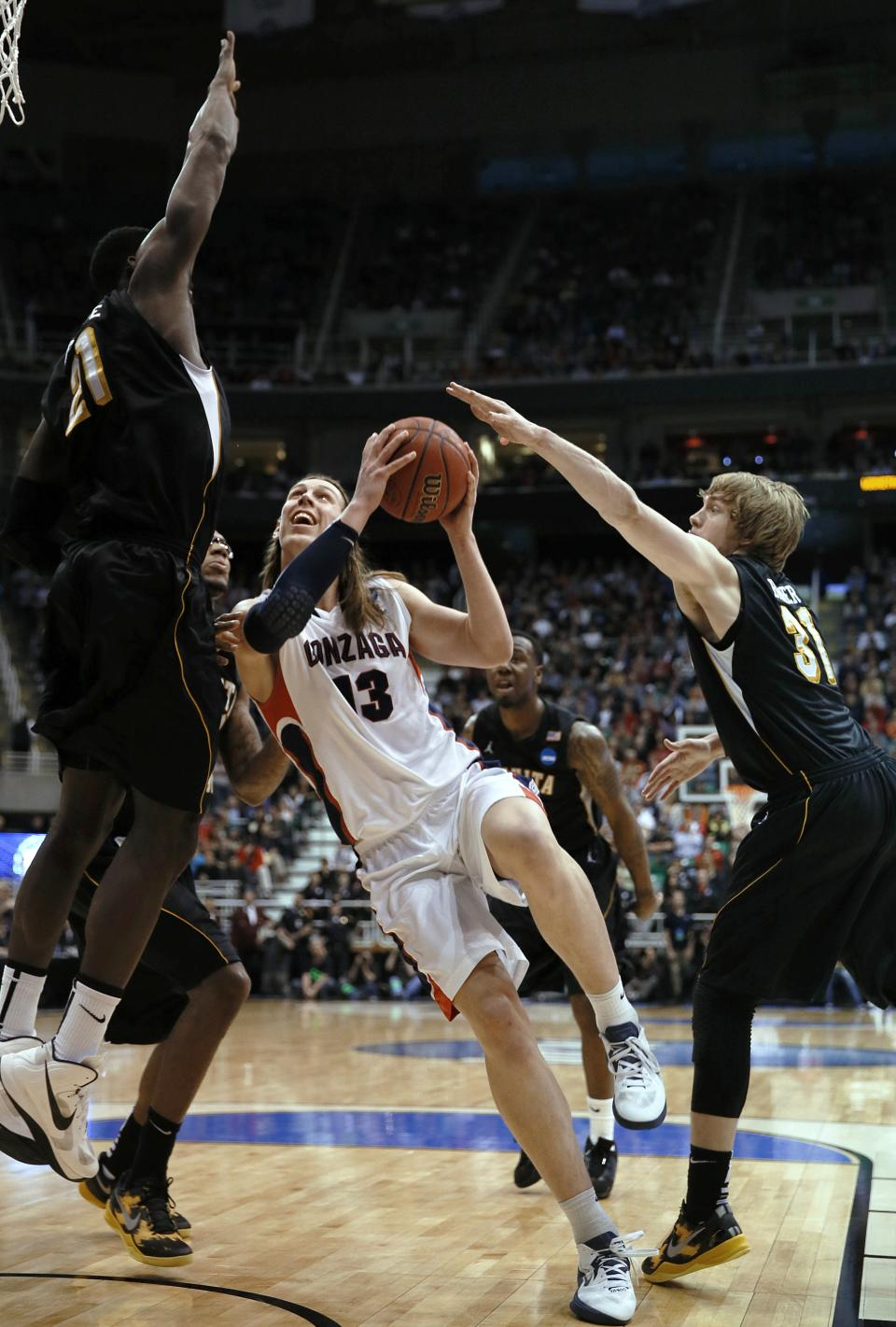 Gonzaga's  Kelly Olynyk, center, drives between Wichita State's  Ehimen Orukep, left and Ron Baker during the first half during a third-round game in the NCAA men's college basketball tournament in Salt Lake City on Saturday, March 23, 2013. (AP Photo/George Frey)