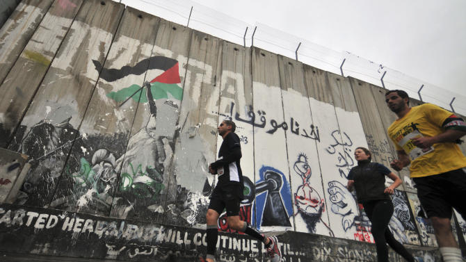 People run past the separation wall during the West Bank's first marathon in Bethlehem, Sunday, April 21, 2013. About 1,000 people participated in the race, which included shorter 10-kilometer and 20-kilometer options. (AP Photo/Mahmoud Illean)