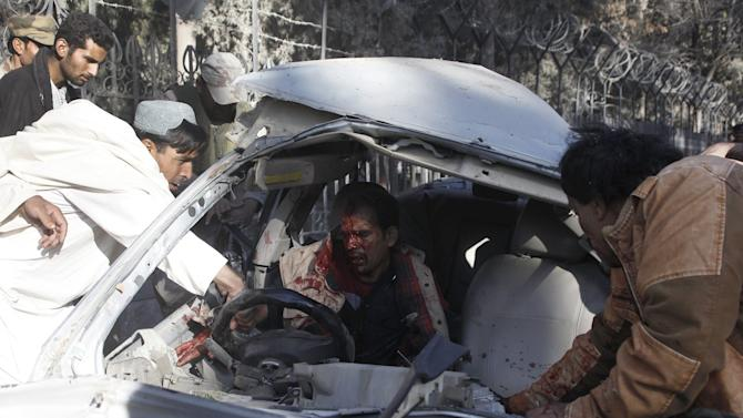 People try to help get an injured man out of his car after a blast in Quetta