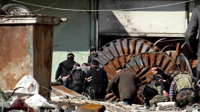 This citizen journalism image provided by Aleppo Media Center AMC which has been authenticated based on its contents and other AP reporting, shows members of the free Syrian Army hiding behind scrap metal during an attack against Syrian government forces, in the neighborhood of al-Amerieh in Aleppo, Syria, Sunday, April. 21, 2013. The Syrian opposition called on Hezbollah to withdraw its fighters from the country immediately, as activists said regime troops supported by pro-government gunmen linked to the Lebanese Shiite militant group battled rebels Sunday for control of a string of villages near the Lebanon-Syria border. (AP Photo/Aleppo Media Center AMC)