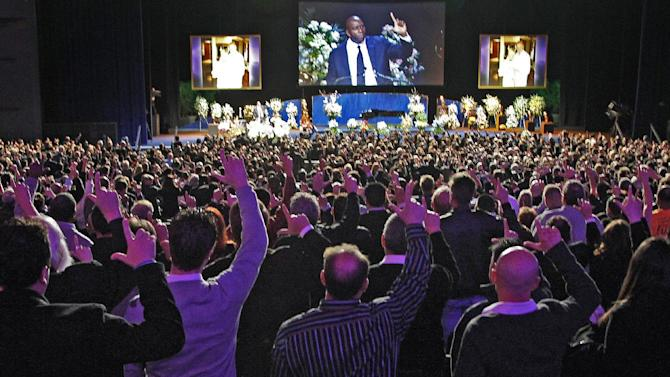 """Attendees stand and gesture with Hall of Famer Earvin """"Magic"""" Johnson during a memorial service for Jerry Buss, the late Lakers owner who died Monday from cancer complications, Thursday, Feb. 21, 2013, in Los Angeles. (AP Photo/Reed Saxon)"""