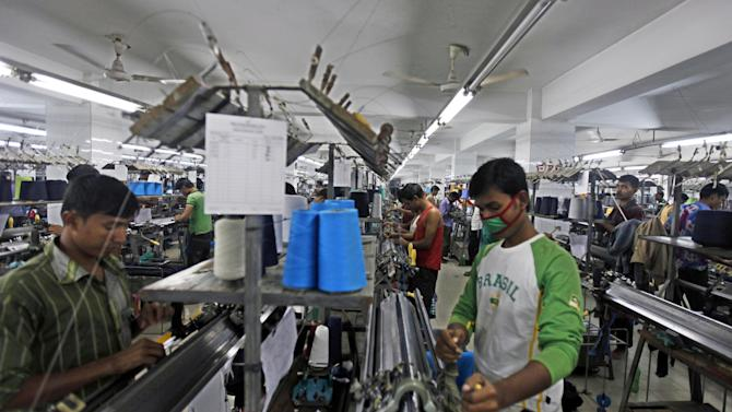 "In this Saturday, Dec. 8, 2012, photo, Bangladeshi garment workers manufacture clothing in a factory on the outskirts of  Dhaka, Bangladesh. About a year before a November fire at a clothing factory in Bangladesh killed 112 people, executives from Wal-Mart, Gap and other big clothing companies met nearby in the country's capital to discuss a legally binding contract that would govern safety inspections. But after a spokeswoman for Wal-Mart, the world's largest retailer, got up and said the proposal wasn't ""financially feasible,"" the effort quickly lost momentum. (AP Photo/A.M. Ahad)"