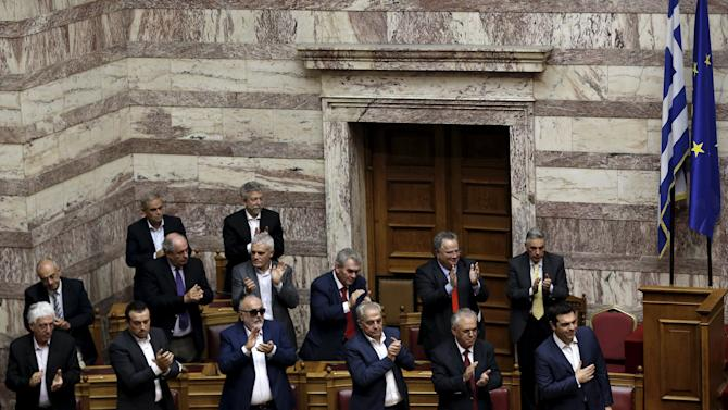 Greek Prime Minister Alexis Tsipras acknowledges the applause by ministers of his government following his speech during a parliamentary session before a vote of confidence at the parliament building in Athens