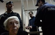 Mikhail Kosenko, one of the activists accused of violence at a rally, stands in a defendant's cage in a court in Moscow on October 8, 2013, as Moscow Helsinki Group president Lyudmila Alekseyeva (front) attends the trial
